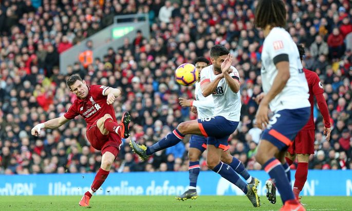 James Milner L of Liverpool shoots during the Premier League match at Anfield Stadium Liverpool