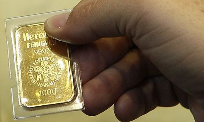 Man holds 250g gold bar after unveiling of gold-plated ATM in Munich bank