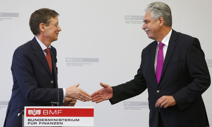 Austria's Finance Minister Schelling and spokesman for the umbrella group of Heta creditors Munsberg shake hands after a news conference in Vienna