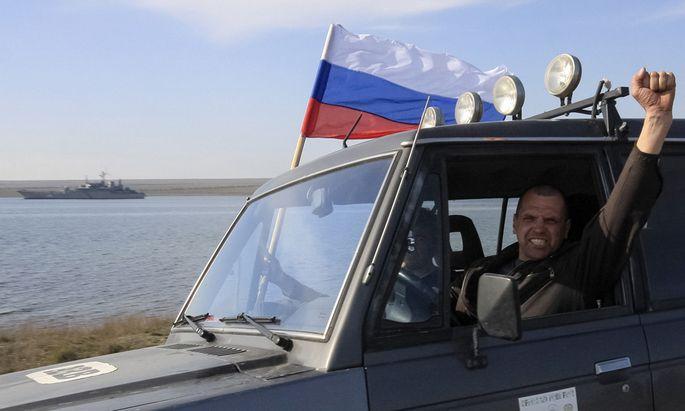 A member of a pro-Russian self defence unit gestures as he drives past the Ukrainian naval landing vessel ´Konstantin Olshansky´ in Donuzlav bay in Crimea