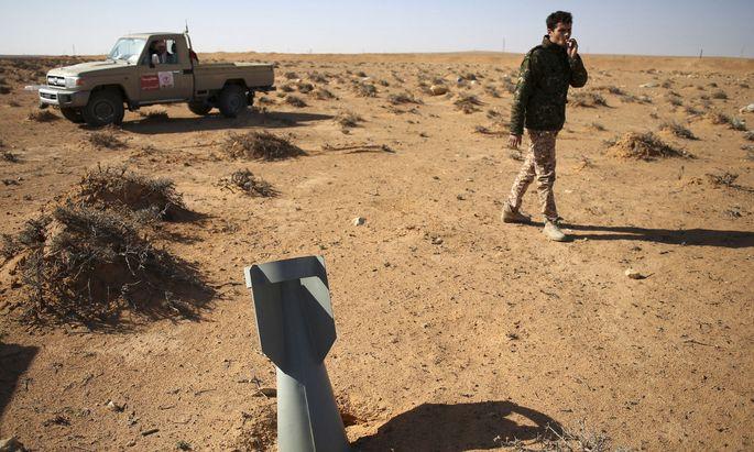 Ein libyscher Kämpfer spaziert nach einem Luftangriff an einem Blindgänger vorbei. Die Bürgerkriegswirren in dem nordafrikanischen Land verstärkten den Einfluss extremistischer Kräfte.
