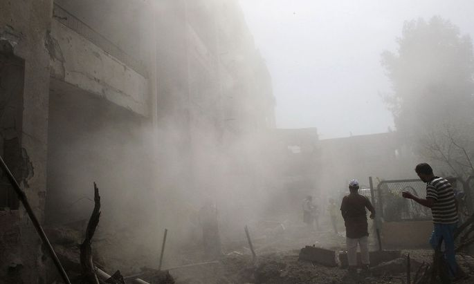 People inspect a site hit by what activists said were missiles fired by Syrian Air Force fighter jets loyal to President Bashar al-Assad, in Raqqa province, eastern Syria