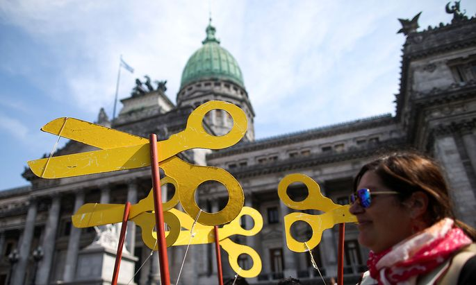 A demonstrator holds scissors cutouts during a national teachers´ strike outside of the National Congress, in Buenos Aires