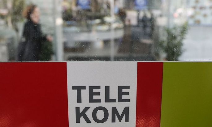 A woman makes a phone call behind a sign of Telekom Austria in Vienna