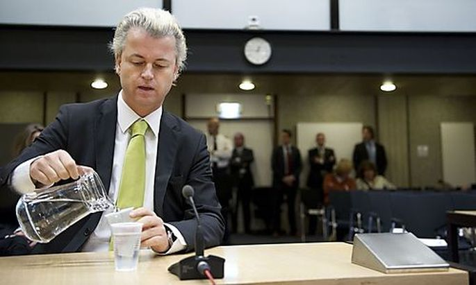 Dutch lawmaker Geert Wilders, charged with inciting hatred against Muslims, pours water in a courtroo