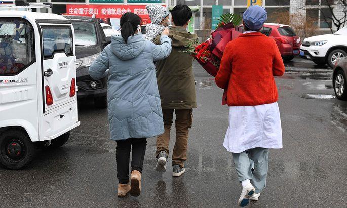 Familie Liu (links mit Kind) war an den neuen Coronaviren erkrankt. Nach mehreren Tagen im Pekinger Youan-Spital wurden die Lius am Freitag entlassen.