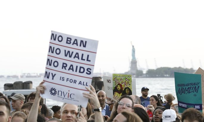 People hold placards during a protest against U.S. President Donald Trump's immigration policies in New York City