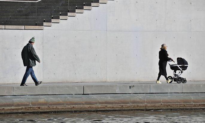 Mann, Frau mit Kinderwagen an einem Fluss in einer Stadt Frau mit Kinderwagen vor einer Treppe an einem Fluss in einer S