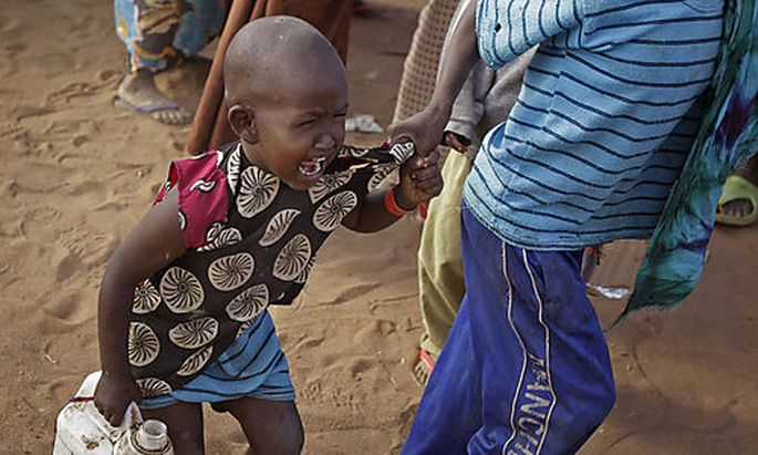 A child cries out as his brother pulls him after they were handed food at a World Food Programme, WFP
