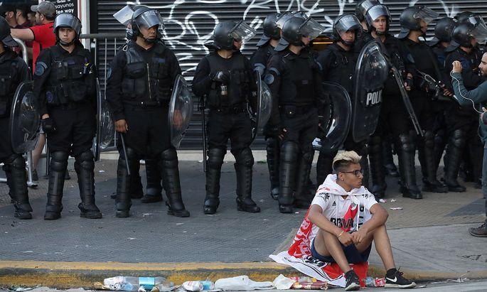 Ein Fan sitzt vor Polizisten am Boden
