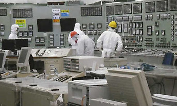 People work in the control room of reactor No. 2 with restored lighting at the earthquake and tsunami