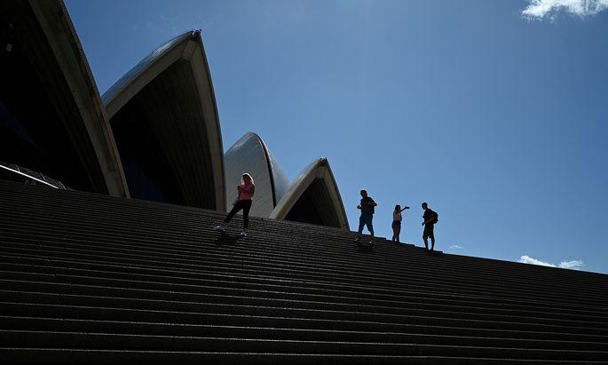 Eine Handvoll Touristen auf den Stufen der verwaisten Oper von Sydney.