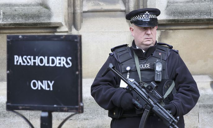 An armed police officer stands on duty outside St Stephen´s entrance to the Houses of Parliement, in London