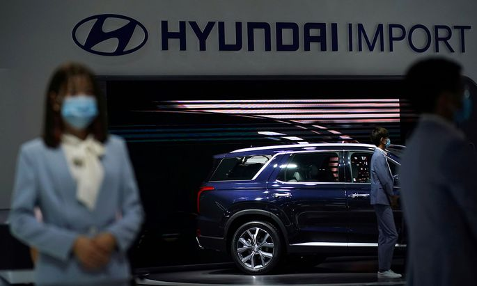 Staff members wearing face masks are seen at a Hyundai booth at the Beijing International Automotive Exhibition, or Auto China show, in Beijing
