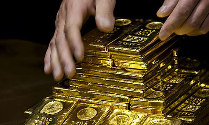 A staff member displays gold bullion bars during a news conference at the Chinese Gold and Silver Exc