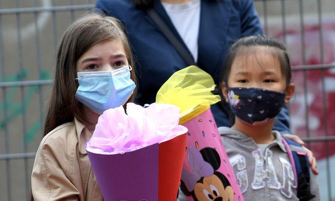 Erstklässlerinnen mit Schultüte und Mund-Nasenschutz