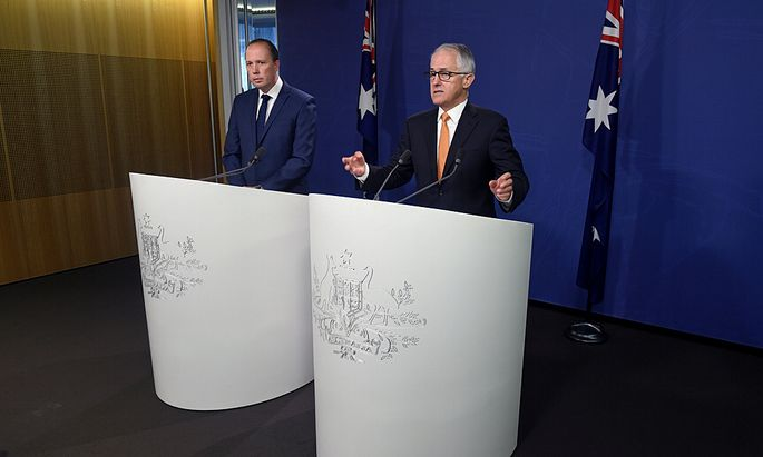 Australian Prime Minister Malcolm Turnbull speaks as he stands with Immigration Minister Peter Dutton during a media conference in Sydney