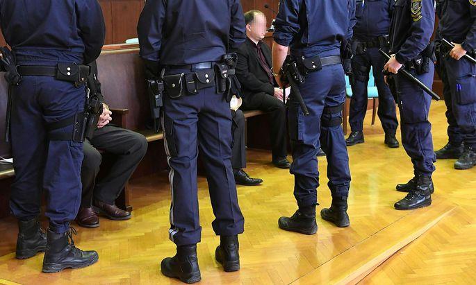 Die Angeklagten mit Polizisten im Gerichtssaal.