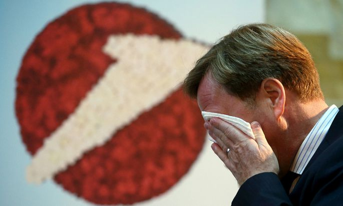 UniCredit unit Bank Austria Chief Executive wipes his face as he passes a company logo before a news conference in Vienna