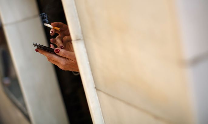 Woman smokes a cigarette as she holds a smartphone in the Andalusian capital of Seville