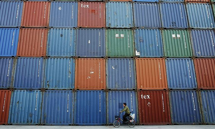 File photo of a man riding a bicycle past containers at a port in Shanghai