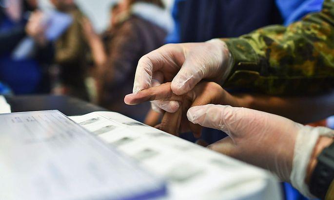 In Heidelberg nimmt die deutsche Polizei Fingerabdrücke von Flüchtlingen.