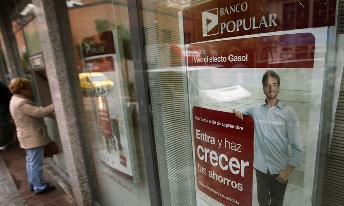 A woman withdraws money from an ATM at a Spanish Banco Popular branch in Madrid