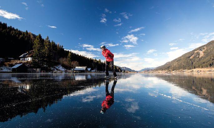 """Wenn sich der Himmel im Eis spiegelt, und man durch die dicke Eisdecke bis zum Grund des glasklaren Sees schauen kann, dann spricht man am Weissensee vom """"schwarzen Eis"""" oder dem """"Spiegeleis""""."""