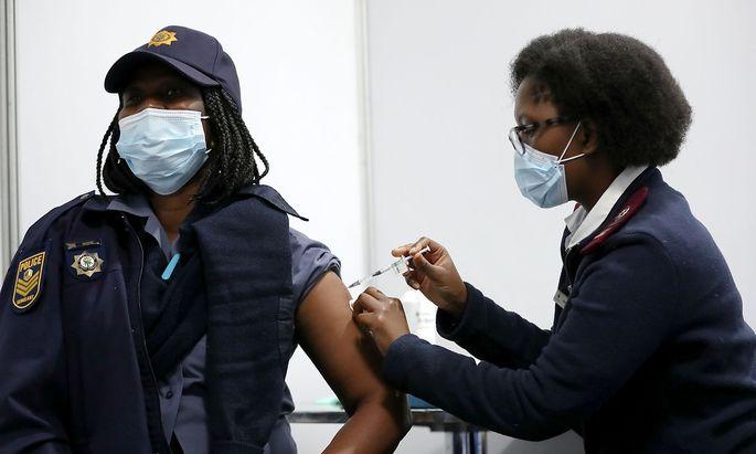 Eine südafrikanische Polizistin erhält in Soweto eine Covid-Impfung.