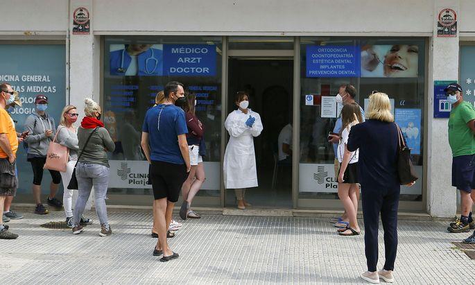 Tourists queue outside a coronavirus disease (COVID-19) test site in Playa de Palma beach