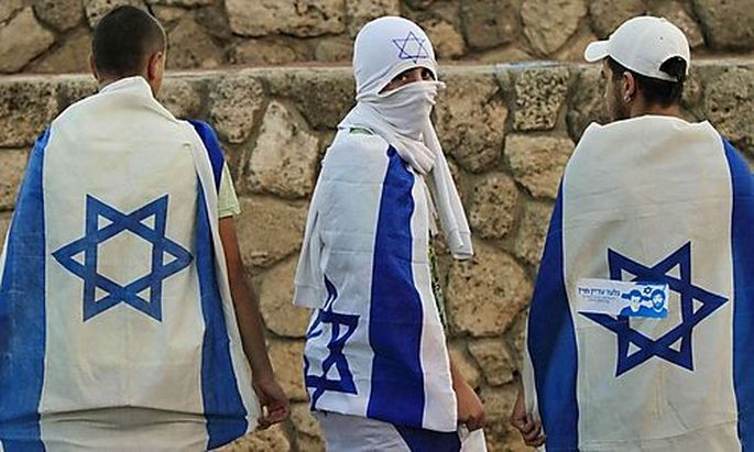 Israelis wrapped with the national flag in support of Israel gather in Ashkelon, southern Israel, Thu