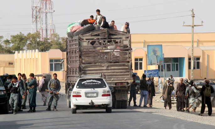 Afghan residents sit on a truck as they leave their home after a battle with the Taliban in Kunduz Province, Afghanistan