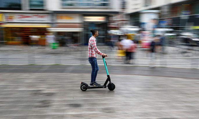 A user rides an e-scooter from provider Tier in a pedestrian area in Frankfurt