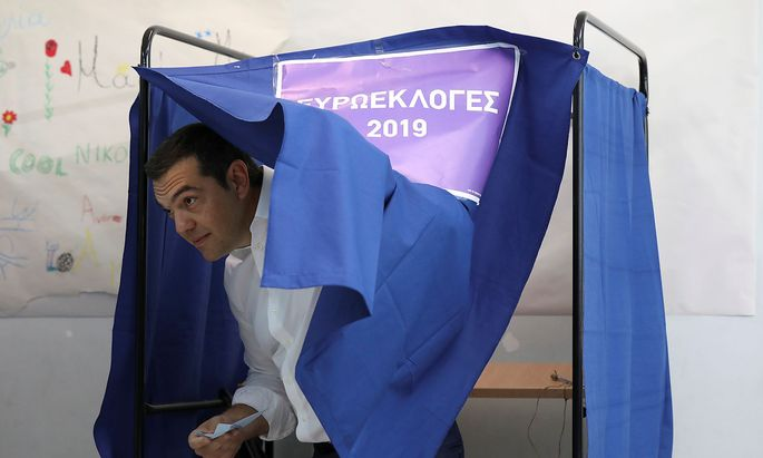 Greek PM Tsipras exits the polling booth before voting for the European and local elections at a polling station in Athens