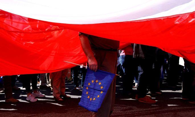 Ein Demonstrant steht mit der EU-Flagge unter einer riesigen weiß-roten Fahne Polens.