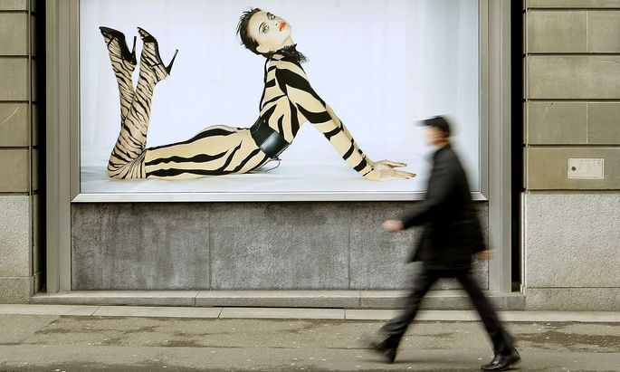A man walks past an advertising poster of Austrian luxury hosiery group Wolford AG in Zurich