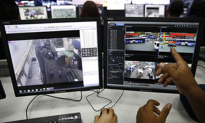 A Venezuelan official points at a monitor screen at the headquarters of SIMA in Caracas