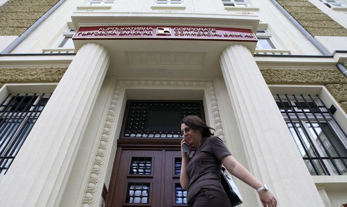 Woman walks in front of the main office of Bulgaria's Corporate Commercial Bank in Sofia