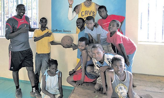 Lale Labuko und mehrere der Mingi- Kinder, die er vor dem Tod gerettet und bei sich aufgenommen hat, um ihnen ein sicheres Heim und Schulbildung zu geben.