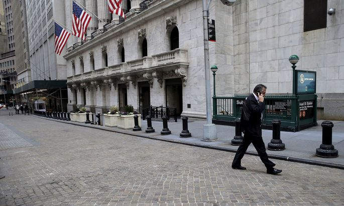Trader walks outside New York Stock Exchange (NYSE) before opening bell of trading session in New York