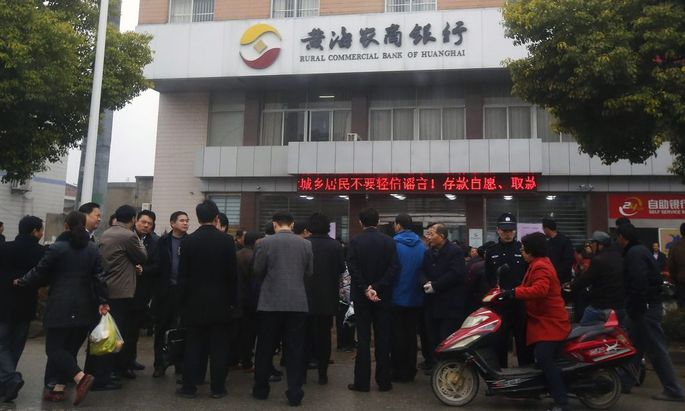 People gather in front of a branch of Rural Commercial Bank of Huanghai in Yancheng, Jiangsu province