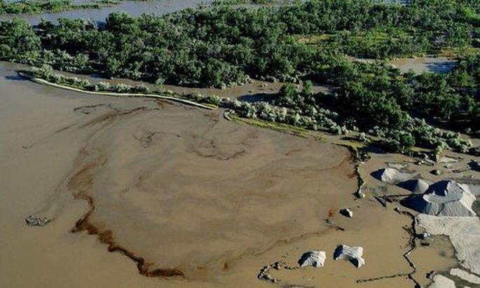 Oil swirls in a flooded gravel pit in Lockwood, Mont. after a pipeline break early Saturday, July 2,