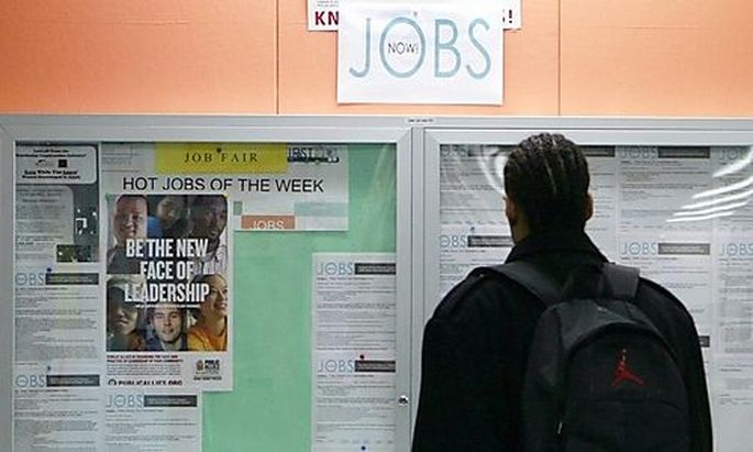File photo of a man looking at employment opportunities at a jobs center in San Francisco