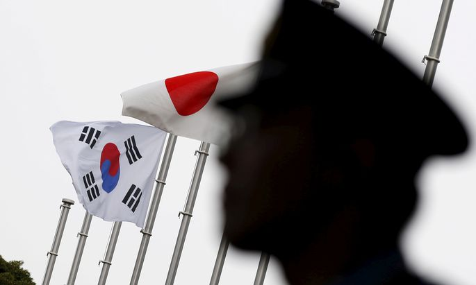 FILE PHOTO: Police officer stands guard near Japan and South Korea national flags at hotel, where South Korean embassy in Japan is holding the reception to mark the 50th anniversary of normalisation of ties between Seoul and Tokyo, in Tokyo