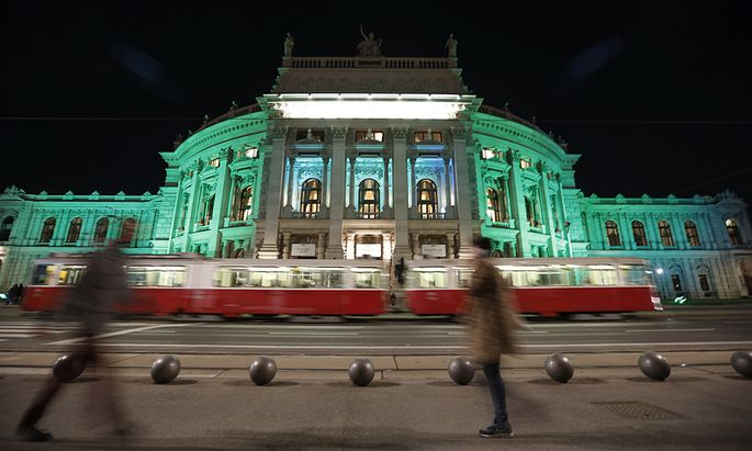 Two pedestrians pass by Burgtheater which is lit in green in celebration of St. Patrick´s day, in Vienna