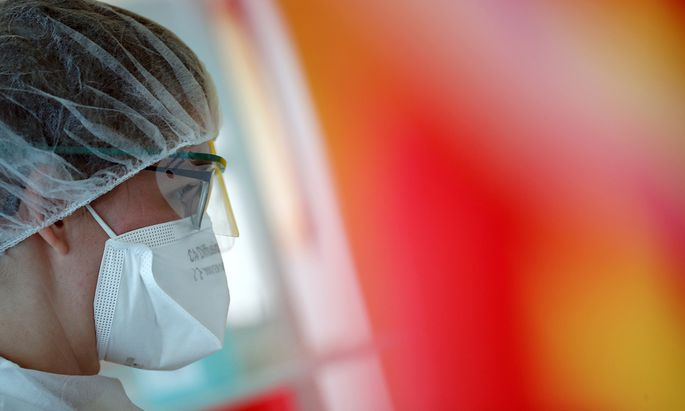 A medical worker, wearing a protective face mask and a protective suit, works in a pulmonology unit at the hospital in Vannes