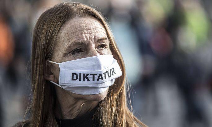 """Frau mit """"Diktatur""""-Maske"""