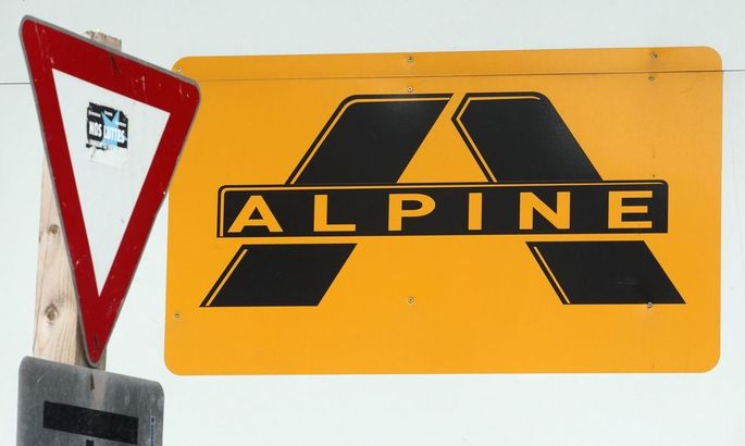 A logo of Alpine Bau is pictured next to a traffic sign at a construction site in Vienna