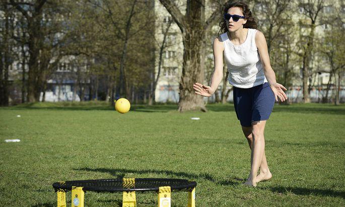 Eine junge Frau spielt Roundnet im Park, auch Spikeball genannt.