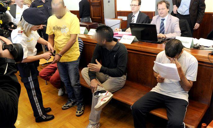 Beschuldigte auf der Anklagebank vor Beginn eines Prozesses wegen Schlepperei
